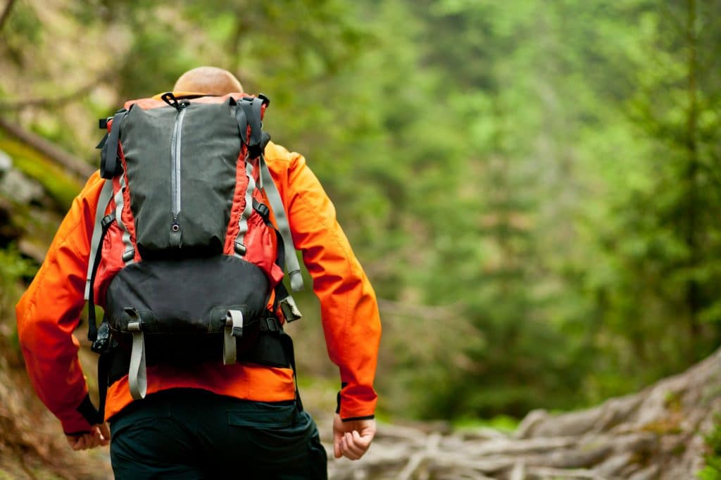 Young man in orange jacket walking hiking outdoors with backpack