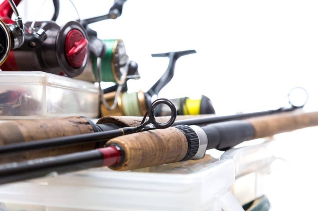 different fishing reels and rods on storage boxes with fishing baits and lures