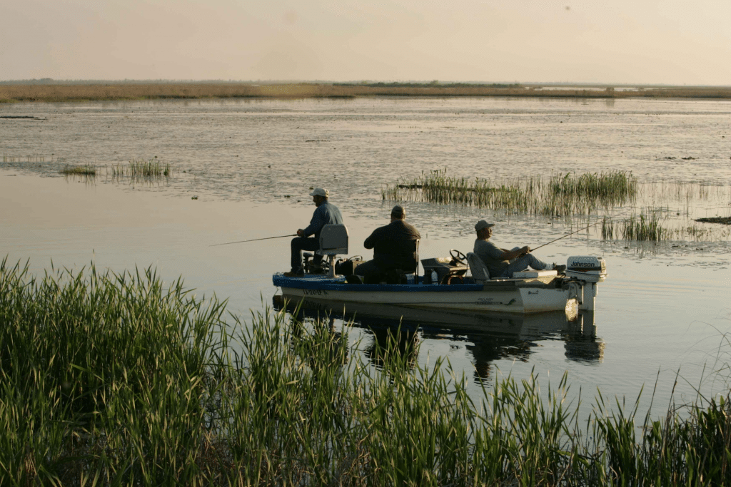 Three men sitting in boat and fishing in the river