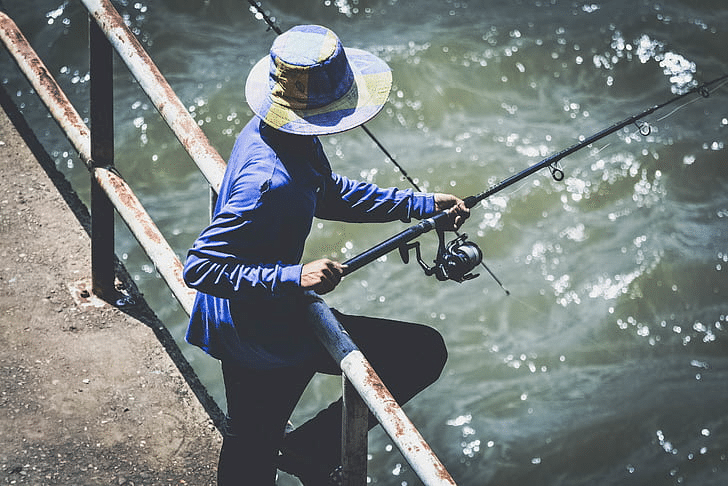 Man fishing from a bridge with a travel rod