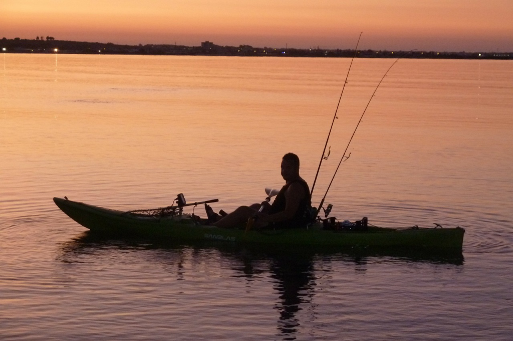 Man fishing in kayak under sunrise