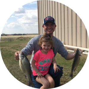bass fishing expert Wesley Littlefield smiling with his daughter holding two bass fish