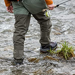 walking through a stream with the best fishing waders